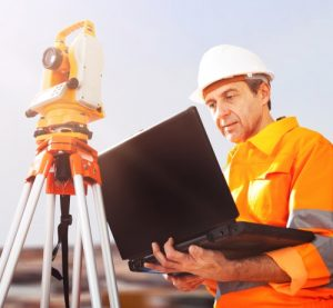 Surveyor working with Theodolite and Laptop